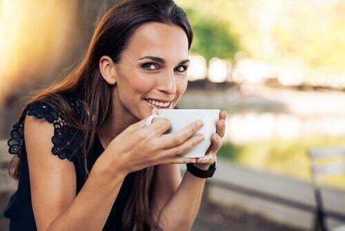 Kobieta pije kawę, by odzyskać energię