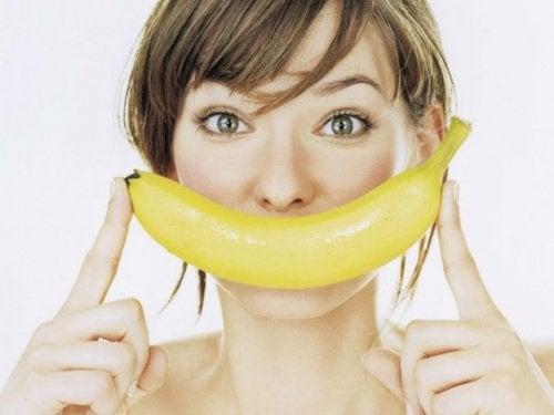 Kobieta trzyma banana przy twarzy jakby się uśmiechała