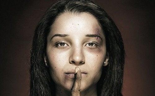 znęcanie się nad kobietami, kobieta pobita pokazuje cisze