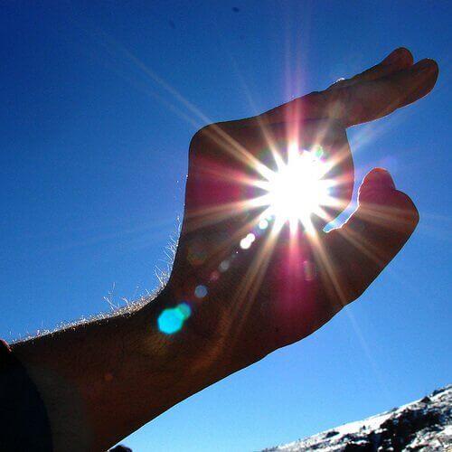 Promienie słoneczne prześwitujące przez dłoń.