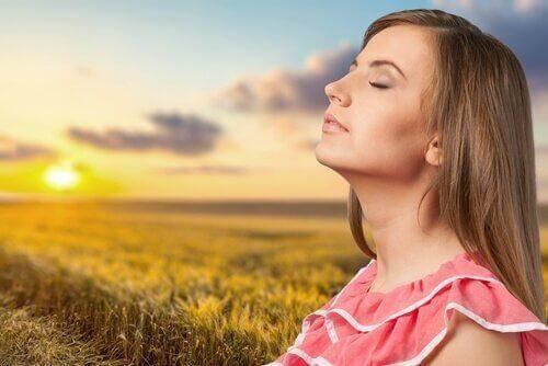 Kobieta relaksuje się na łące o zachodzie słońca