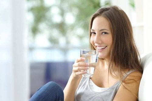 uśmiechnięta kobieta ze szklanką wody
