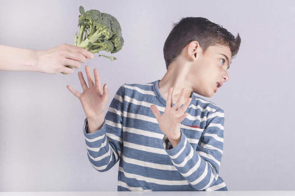 Chłopiec odrzucający warzywa.