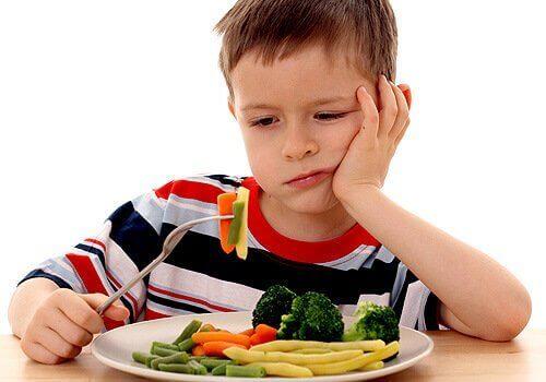 Chłopiec patrzący na warzywa z niechecią.