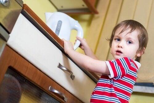 dziecko bierze czajnik z wodą  a oparzenie