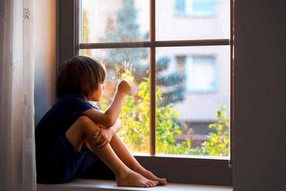 Dziecko patrzące przez okno i jego traumy emocjonalne