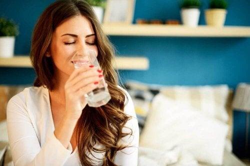 kobieta pije wodę, aby mieć gładką skórę