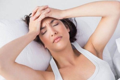 kobieta w łóżku z bólem głowy