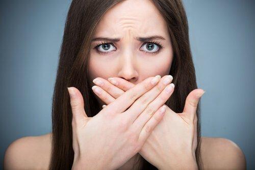 Nieświeży oddech, kobieta zakrywa usta