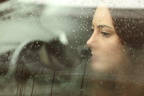 smutna kobieta za szybą, emocjonalny ból