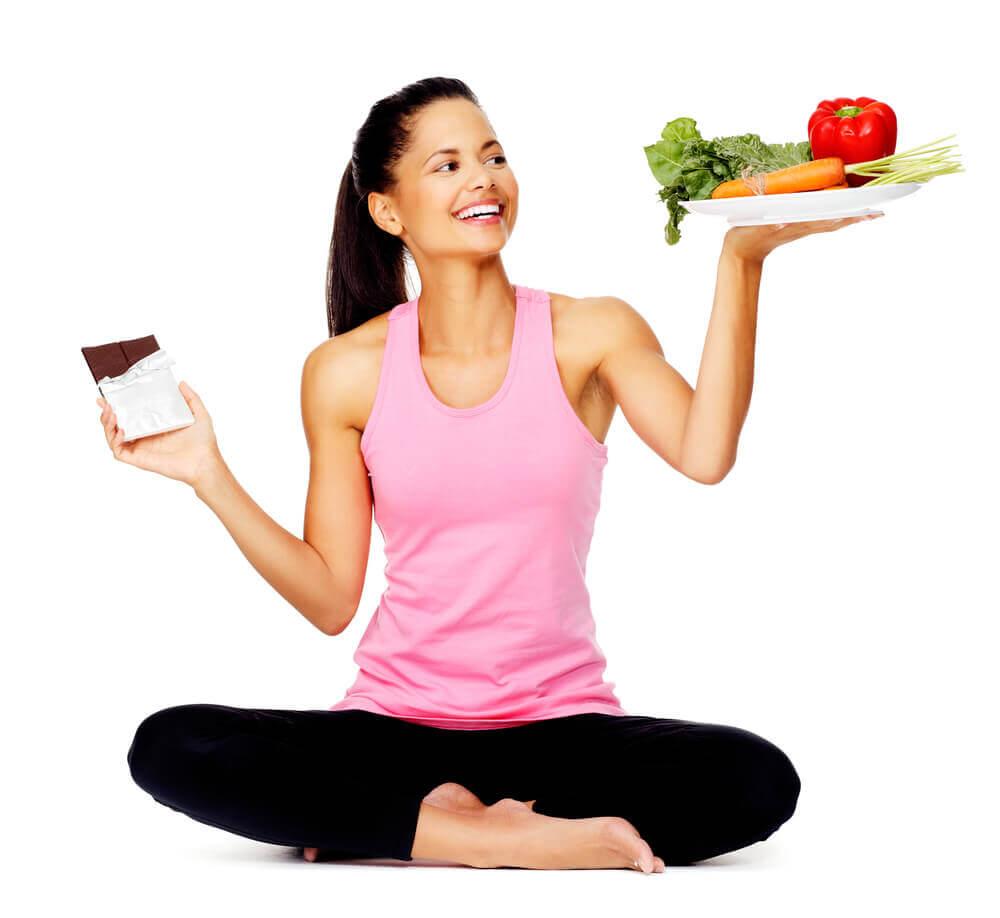 Dziewczyna z talerzem warzyw i tabliczką czekolady