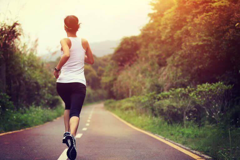 Kobieta biegnąca drogą.