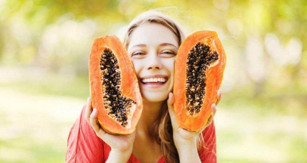 Kobieta trzyma dwie połówki papai
