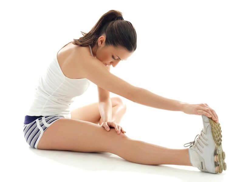 Kobieta rozciąga mięśnie nóg i pleców