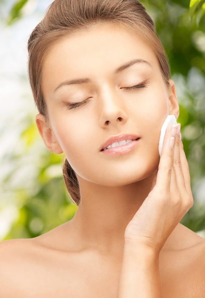 Kobieta przeciera twarz wacikiem