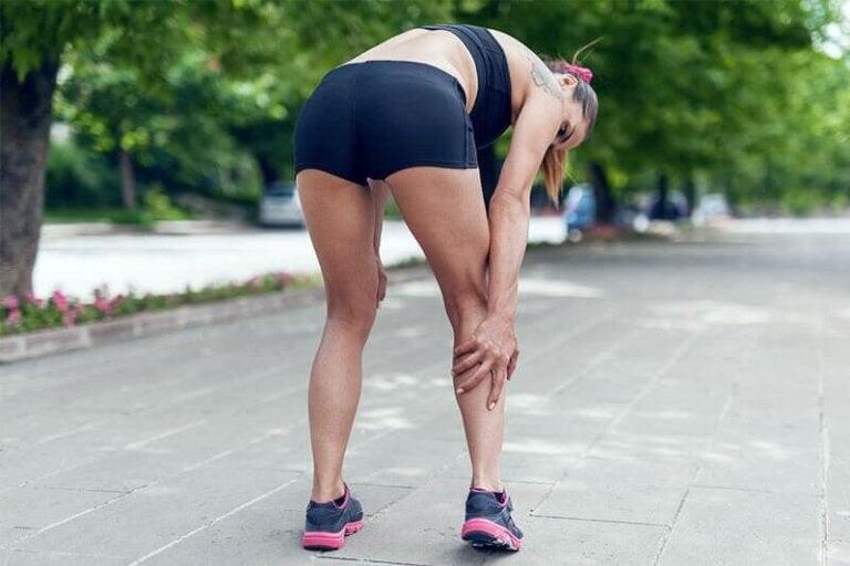 Kobieta odczuwająca ból nogi spowodowany przez zapalenie ścięgna Achillesa