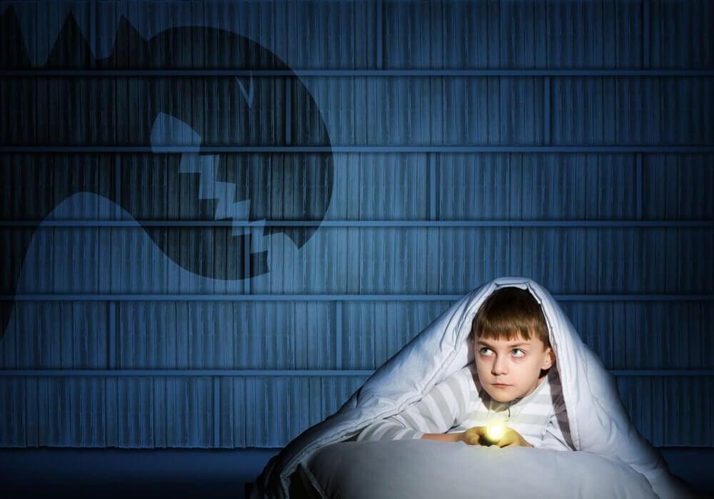 Chłopiec w łóżku z latarką i potwór na ścianie