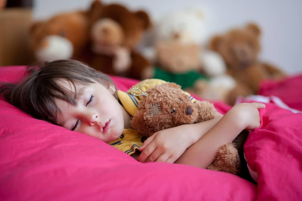 Dziewczynka śpi z misiem