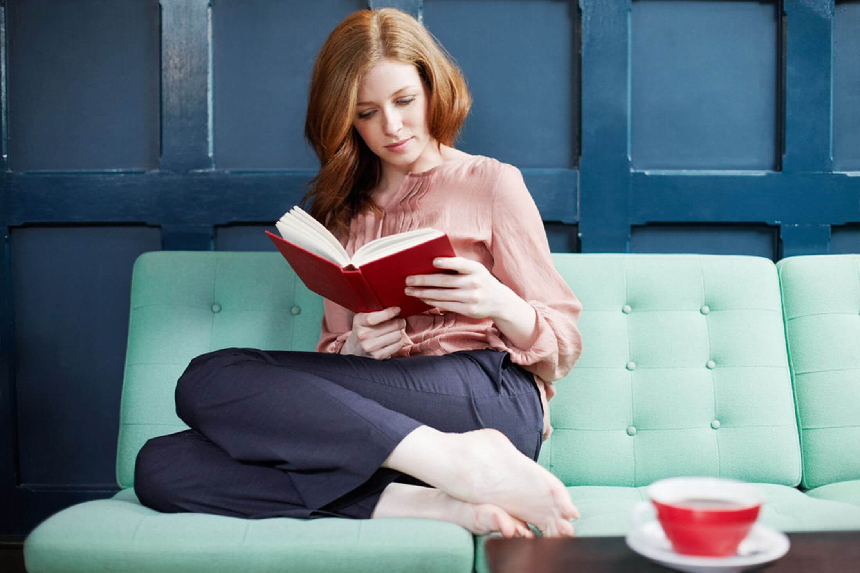 kobieta czytająca książkę na kanapie
