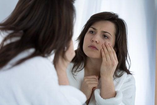 Kobieta ogląda twarz w lustrze