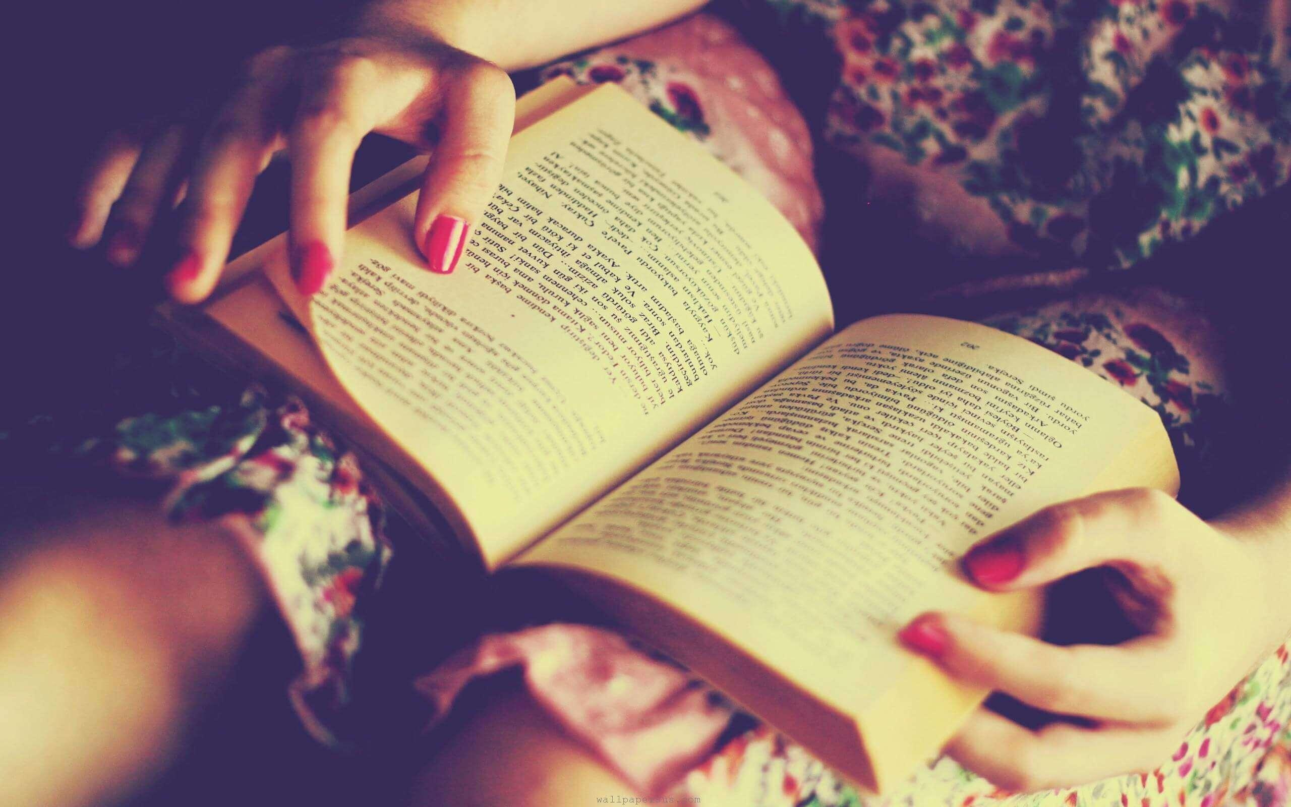 książka na kolanach i czytanie w nocy