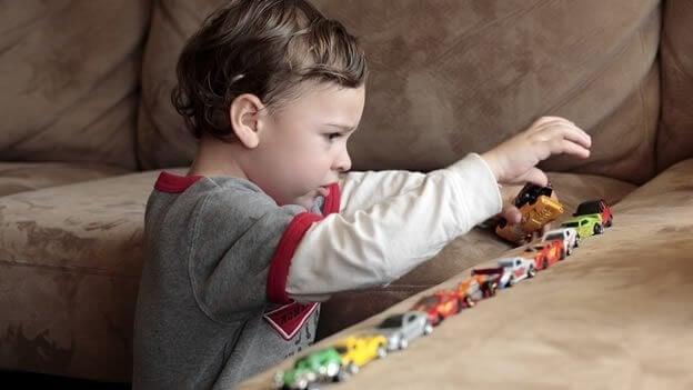 Dziecko z autyzmem układa zabawki w linii prostej