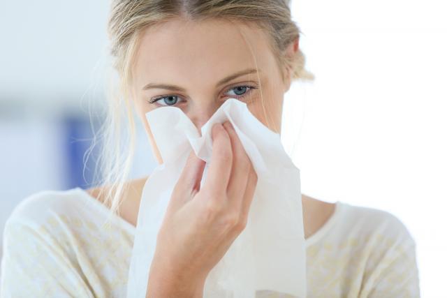 Kobieta wycierająca nos