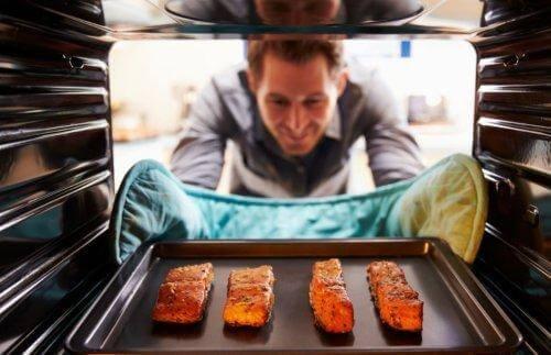 Mężczyzna wyciąga łososia z piekarnika