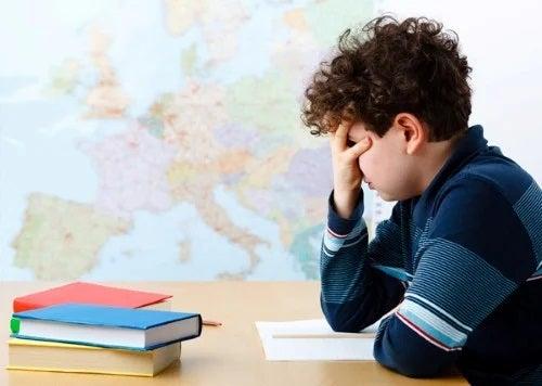 Chłopiec zakrywa twarz podczas nauki