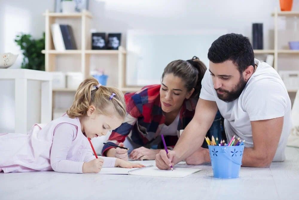 Dziewczynka z rodzicami odrabia zadania