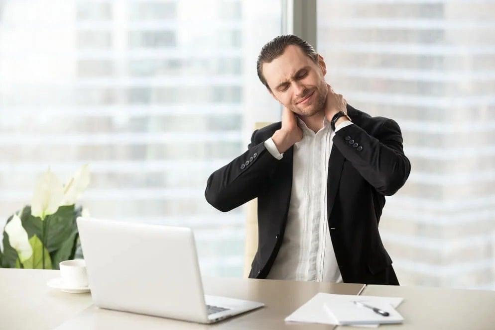 Mężczyzna z bólem karku w pracy