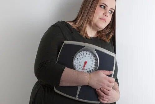 Otyła kobieta trzyma wagę