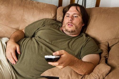 Otyły mężczyzna przed telewizorem.