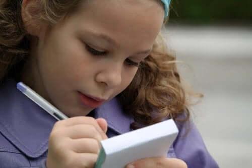 Dziewczynka zapisuje coś w notesie