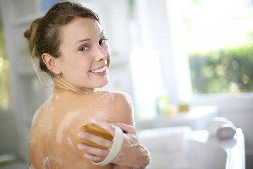 Kobieta myje piękne plecy bez trądziku