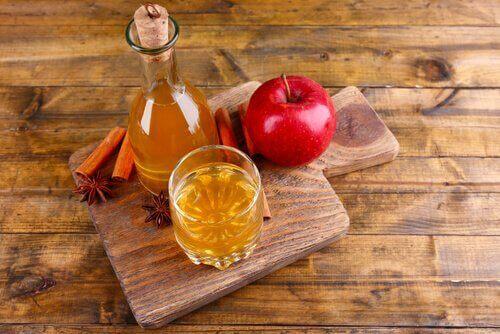 Ocet jabłkowi i jabłko na desce