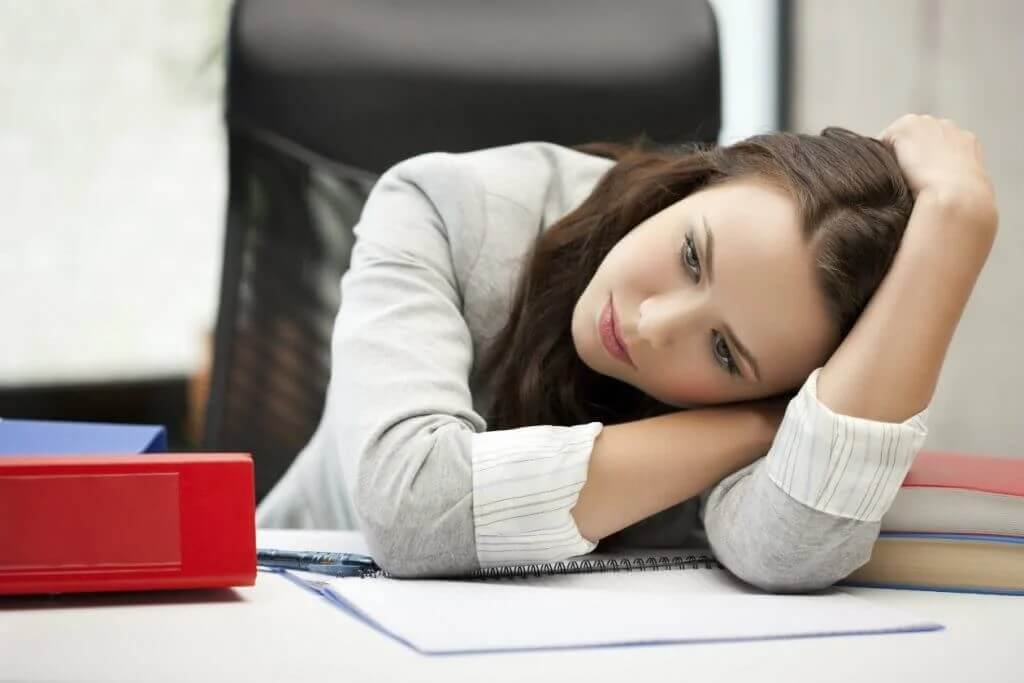 Smutna kobieta opiera się o biurko
