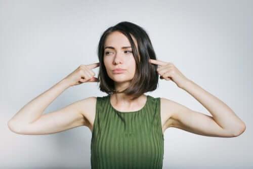 Kobieta zatyka uszy - hałas