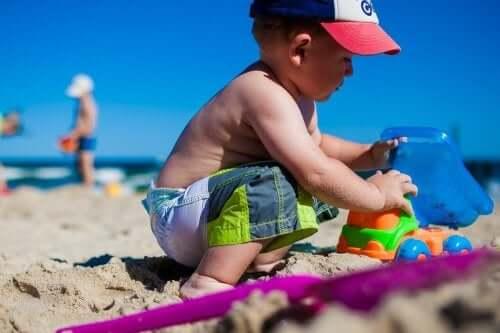 Chłopiec bawi się w piasku na plaży