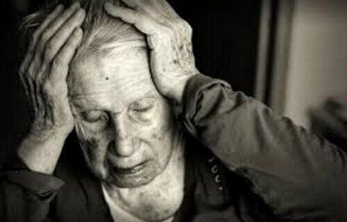 Starszy mężczyzna trzyma się za głowę