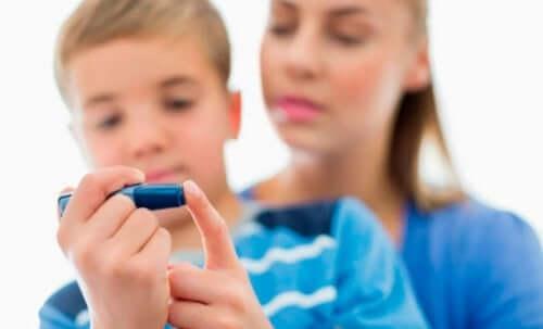 Chłopiec nakłuwa palec - dzieci z cukrzycą