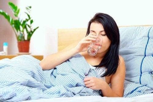 Kobieta w łóżku pije wodę