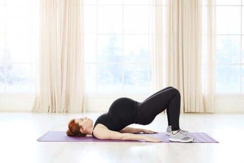 Kobieta ćwiczy na macie pilates podczas ciąży