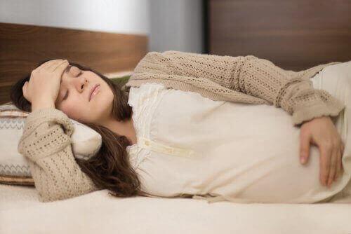 Ciężarna leży na łóżku cierpiąc na ból związany z rwą kulszową