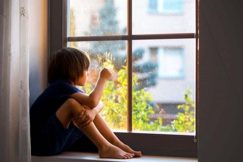 Chłopiec siedzi przy oknie