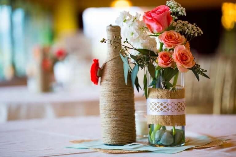 Butelki z kwiatami jako dekoracje pośrodku stołu
