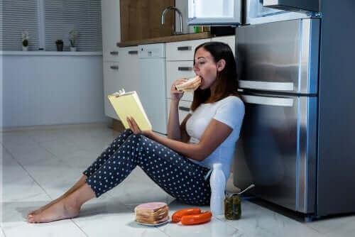 Kobieta objada się przy lodówce, zespół nocnego jedzenia