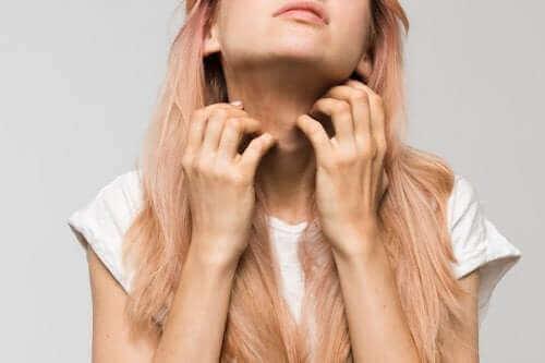 Kobieta drapiąca się po szyi