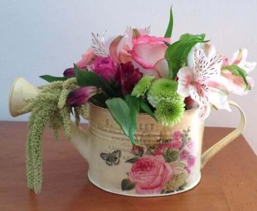 Konewka z kwiatami jako dekoracja pośrodku stołu