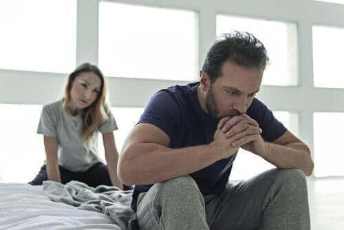 Mężczyzna siedzi zmartwiony na łóżku, a za nim sfrustrowana kobieta.